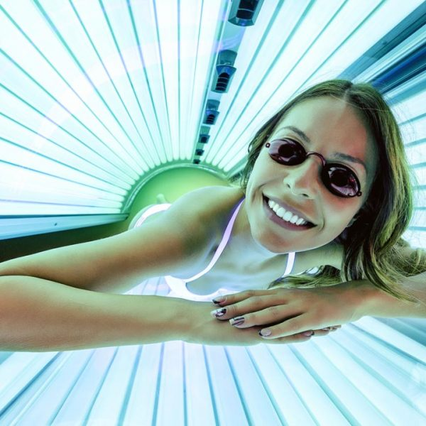 Foxy lady getting a tan in solarium and smiling