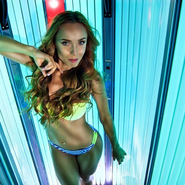blond in the upright tanning bed. ultraviolet lamps with blue light. woman in swimsuit